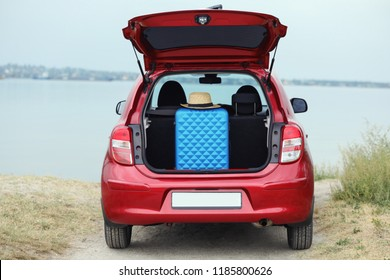 Suitcase and hat in car trunk on riverside