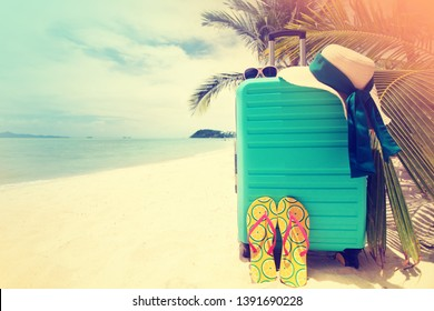 suitcase with hat on tropical beach,sea with palm three in background. Summer holiday traveling concept