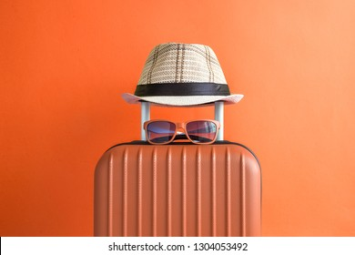 Suitcase with hat and sunglasses on orange background minimal creative travel concept