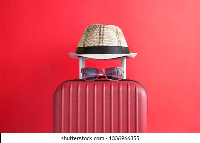 Suitcase with hat and sunglasses on red background minimal creative travel concept