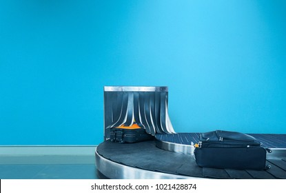 Suitcase or luggage is conveyed through the conveyor belt in arrivals lounge of airport terminal, blue wall