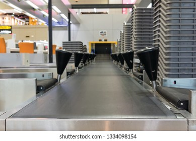 Suitcase on luggage conveyor belt at baggage  handling belt conveyor system at check in desk in airport. Baggage is running on the conveyor belt through an airport safety system.