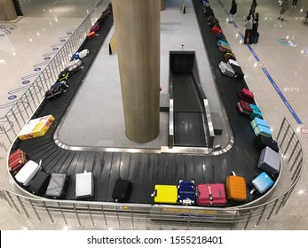 Suitcase on luggage conveyor belt at baggage claim at airport.