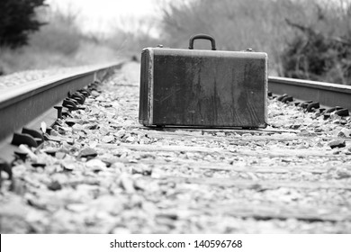 Suitcase On Railroad Tracks - This is a high contrast black and white photo of an old retro suitcase sitting on a set of railroad tracks.