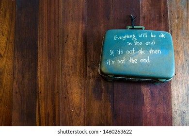 Suitcase on wooden background with as inspirational message written on it.