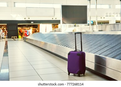suitcase standing near empty conveyor belt at baggage claim at airport