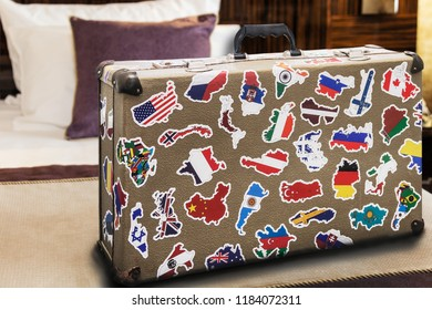 suitcase stickers of the flags of the countries from travels around the world in a hotel room on a bed