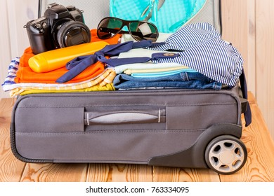 a suitcase stuffed with things for a vacation at sea