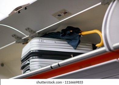 Suitcase and umbrella in overhead hand luggage locker / compartment. Carry-on rules and requirements concept. Air travel.