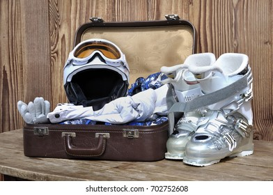 suitcase with winter sports  equipment on wooden background