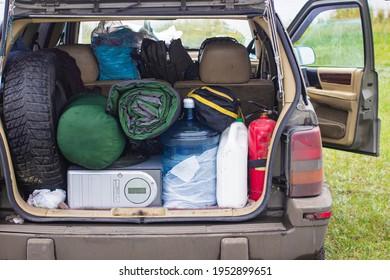 Koffer und Taschen im Kofferraum des Autos bereit für den Urlaub zu fahren. Koffer und Koffer im Kofferraum des Autos, im Freien. Reise, Reisen, Meer. Auto am Strand mit Meer auf Hintergrund