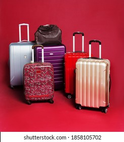 Suitcases different kind of style and size on a composition on a red background
