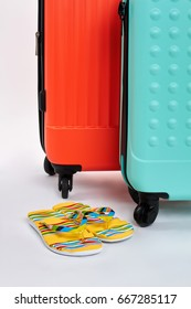 Suitcases, flips close up. Summer sandals and bags on wheel. Concept of summer vacation.
