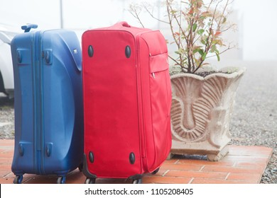 suitcases in front of house ready to go on vacation