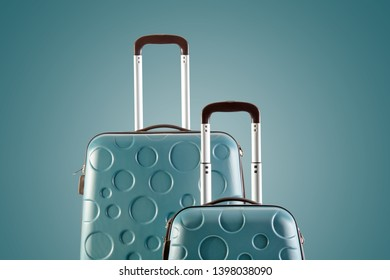 Suitcases isolated on green background close-up. Check-in suitcase and cabin bag. Studio shot.