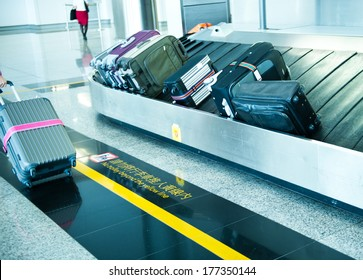 suitcases on conveyor belt of airport.