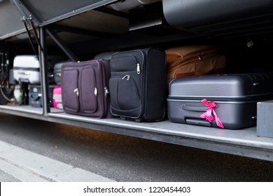 Suitcases stacked in the luggage compartment of a bus