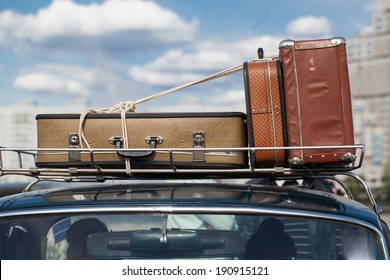 suitcases tied with rope on a car roof