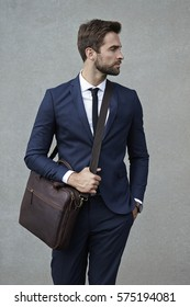 Suited business dude with satchel, looking away