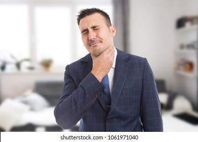 Suited male grabbing painful neck as throat swallowing medical problem and flu cold or influenza concept