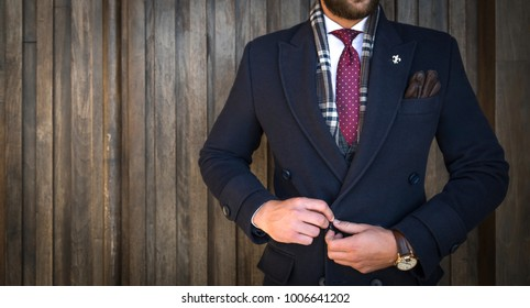 Suited man buttoning his coat and posing in front of wooden background