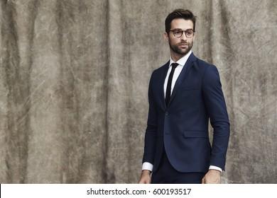 Suited man in eyeglasses, looking away
