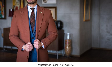 Suited man with tailored trench coat holding his coat and posing indoors