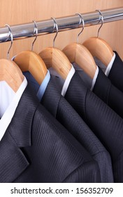 Suits with shirts on hangers on wooden background
