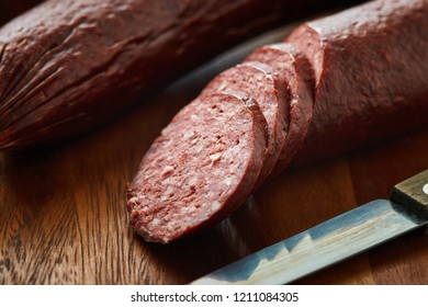 Sujuk (sucuk), a dry spicy sausage on wooden background