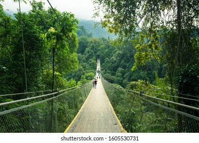 Sukabumi, Indonesia - March 31st 2019: Tourists are walking along Situ Gunung Suspension Bridge, a popular attraction in Sukabumi, West Java, Indonesia