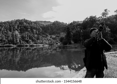 Sukabumi,west java/Indonesia - February 24, 2019 : a photo grapher taking picture at Situ gunung or mountain lake of gede pangrango mount national park in black and white