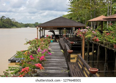 SUKAU, SABAH, MALAYSIA — APRIL 10, 2018. The flower-bedecked dock of Kinabatangan Riverside Lodge fronts the Sungai Kinabatangan (Kinabatangan River) on the island of Borneo.