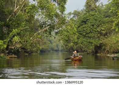 SUKAU, SABAH, MALAYSIA — APRIL 11, 2018. A fisherman paddles his boat on the Sungai Menungal tributary of the Kinabatangan River (Sungai Kinabatangan) with lowland forest vegetation on either side.