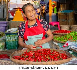 Sukhothai, Tahiland - 2019-03-06 - Jalapeno Vendor Laughs at Market.