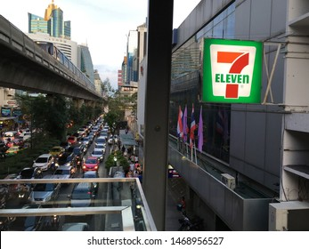 Sukhumvit, Bangkok, Thailand - June, 1, 2019. Bright 7-11, 7 Eleven sign with Sukhumvit, Bangkok traffic jam in background.