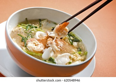 Suki in broth Mixed sea food with vermicelli and vegetable on a chopsticks  ready to eat. on isolated background.