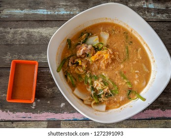 Sukiyaki Thai Style. Pork broth soup boiled with nappa cabbage, morning glory, egg, vermicelli and pork. Serve with Thai spicy sukiyaki sauce. On old wooden table.