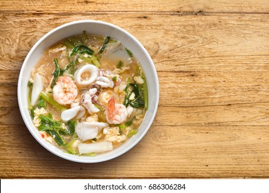 Sukiyaki (Thai Suki) in broth Mixed sea food with vermicelli and vegetables on isolated wooden background.