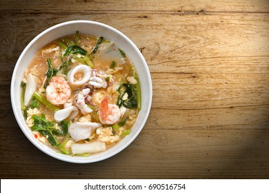 Sukiyaki (Thai Suki) in broth Mixed seafood shirmp, squid with egg vermicelli, vegetables, Chinese Cabbage, tofu, sesame minced sauce, sweet & sour taste, favorite Thai food, isolate wood background