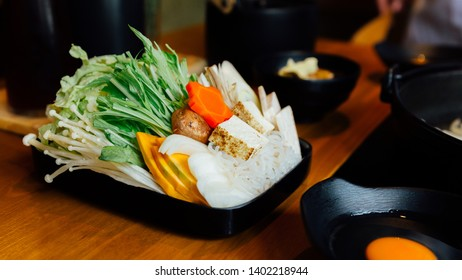 Sukiyaki vegetables set including cabbage, false pak choi, carrot, shiitake, enokitake, tofu, pumpkin, scallion and konjac noodle in black plate.
