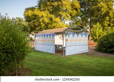 Sukkah decorated with printed pattern, branches date palm and hebrew text of blessing: Grant peace everywhere goodness and blessing, Grace, loving kindness and mercy to us and unto all Israel.