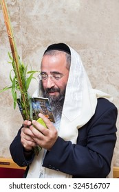 Sukkot. Man holding a lulav and etrog in synagogue . The four species for Sukkot