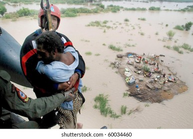 SUKKUR, PAKISTAN - AUG 28: Army officials rescue a man from the flood hit area via helicopter  on August 28, 2010 in Sukkur.