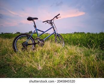 Sukoharjo - Indonesia - 09 - 23 - 2021 A bike on grenn grass against the sky background.
