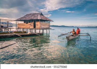 Sulawesi, Indonesia - May 2015: Photo of native men in wooden fishing boat near shore in Malange in Togean islands in Sulawesi, Indonesia. Documentary editorial.