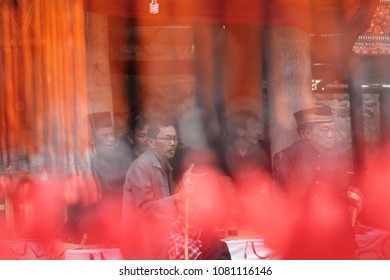 SULAWESI - TANA TORAJA -August 25, 2014 :  group of Torajan man sitting i n traditional costume at a funeral ceremony  in Rantepao view through a colored lamp