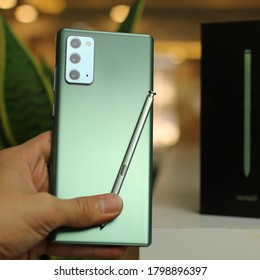 Sulaymaniyah, Iraq - 18 August 2020: A man holding Samsung Galaxy Note20 mystic green with s pen in studio.