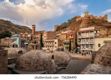 Sulfur baths in the Abanotubani district of Tbilisi. Georgian houses against the background of the fortress Narikala. City landscape at sunrise.