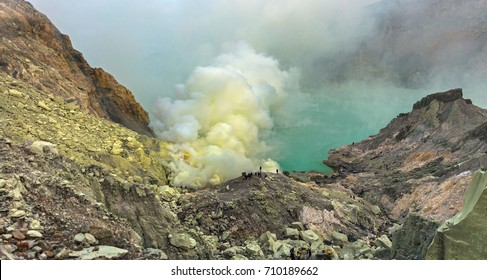 Sulfur mining at Ijen volcano in the night. Blue flame of burning sulfur in the backgroundlake, Tourists and sulfur miners in the foreground. Baluran National Park - Java island, Indonesia