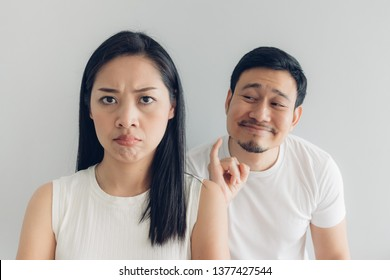 Sulk and reconcile Asian couple lover in white t-shirt and grey background.